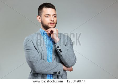 Pensive businessman looking away over gray background