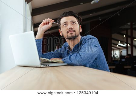 Pensive casual man sitting at the table with laptop and notepad in office