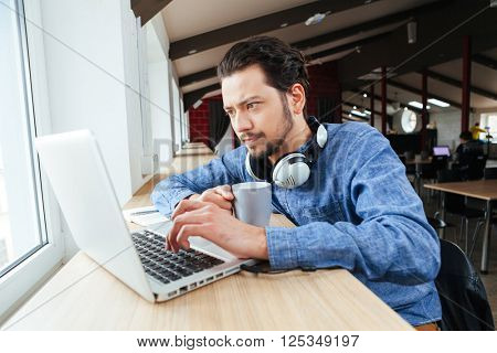 Handsome man using laptop computer in office