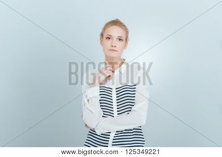 Young blonde woman looking at camera isolated on a white background