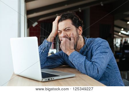 Young man using laptop computer and yawning in office