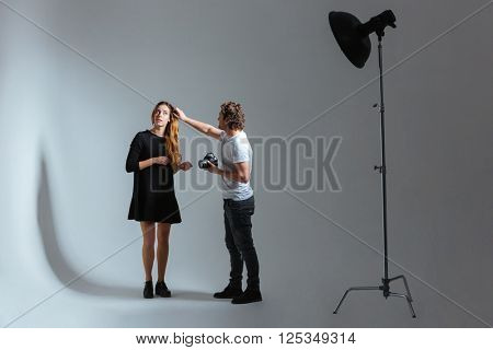 Male photographer working with female model in studio with equipments