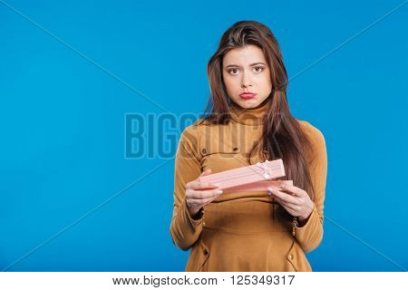Sad disappointed young woman holding opened present box over blue background