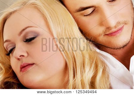 Young couple sleeping on the sofa under blanket