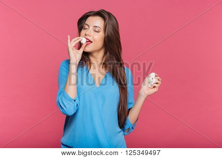 Tender pretty young woman with eyes closed eating sweet candies over pink background