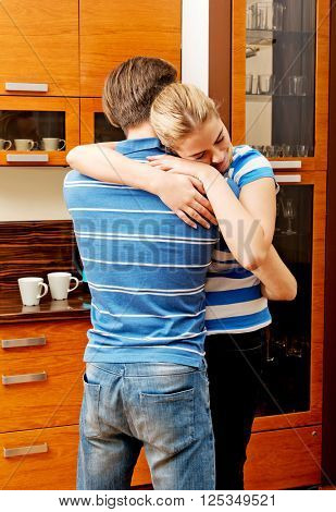 Happy young couple hugging in the kitchen
