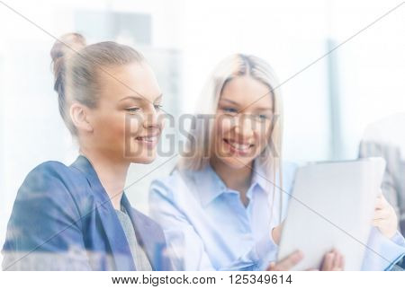 business, technology and office concept - smiling businesswomen with tablet pc computers having discussion in office