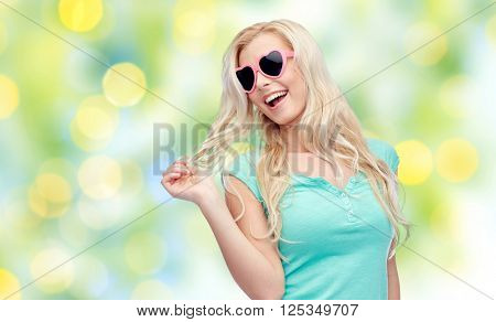 emotions, expressions, summer and people concept - smiling young woman or teenage girl in sunglasses holding her strand of hair over summer green lights background