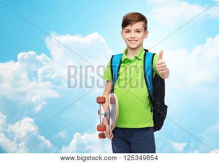 childhood, leisure, gesture, school and people concept - happy smiling student boy with backpack and skateboard showing thumbs up over blue sky and clouds background