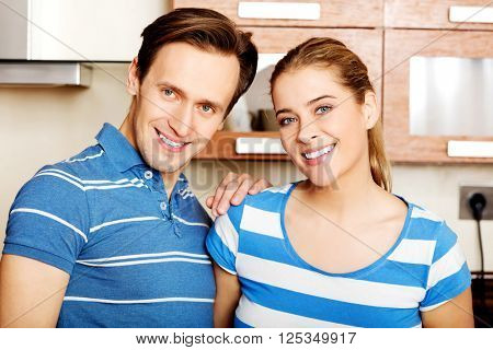 Lovely young couple standing in kitchen