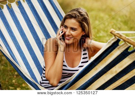 Young woman on hammock talking through a phone