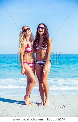 two friends in swimsuits at the beach