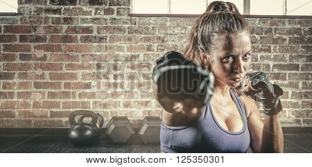 Portrait of female fighter punching against gym