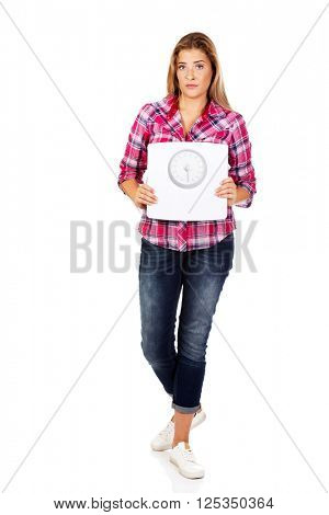 Young sad woman holding weight scale