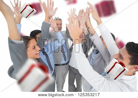 Business people raising their arms against white and red gift box