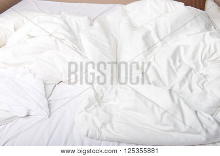 White bedcloth lying on bed