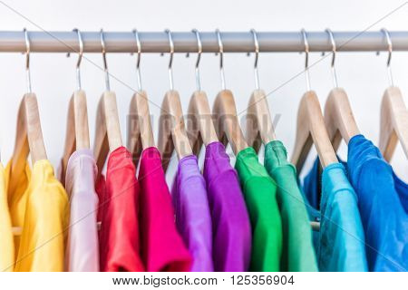 Fashion clothes on clothing rack - bright colorful closet. Closeup of rainbow color choice of trendy female wear on hangers in store closet or spring cleaning concept. Summer home wardrobe. poster