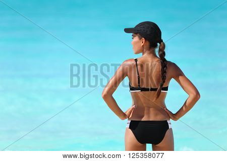 Sexy sporty bikini woman looking over the ocean water for beach watersports. Active healthy Asian girl model standing from behind in swimwear and cap on sunny summer travel vacation.