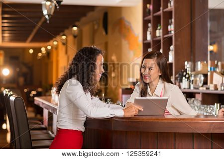 Smiling bar owner and barmaid discussing business ideas
