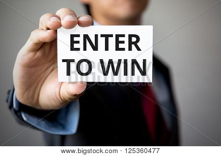 Businessman Presenting 'enter To Win' Word On White Card