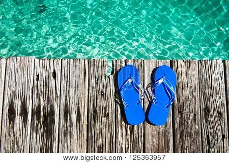 Slippers at jetty by the sea poster