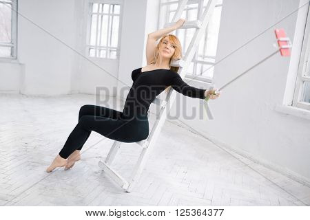 sport, fitness, lifestyle, technology and people concept - young woman in black with smartphone taking selfie whith selfie stick in white gym