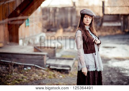 The girl in an old-fashioned outfit wearing flat cap in the courtyard of the wooden barracks, retro look.