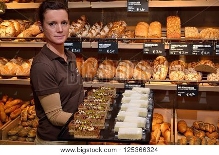 Saleswoman shows selection of cakes breads and pastries in the background