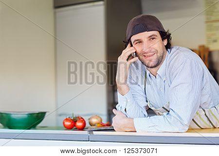 Entrepeneur smiling while making a call on his phone from his takeaway food business