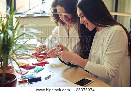 Two beautiful women at the table making jewelry