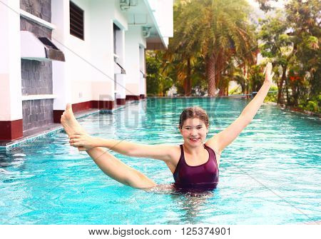 pretty swimmer teenager girl exercise aqua aerobics stretching in swimming pool