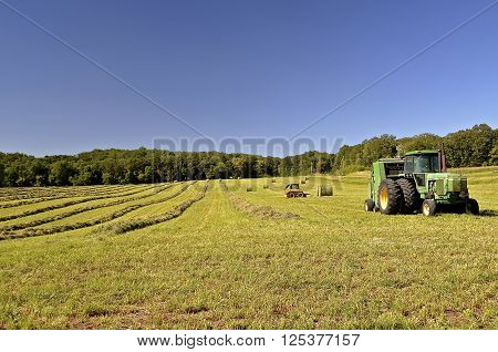 PELICAN RAPIDS, MINNESOTA, August 2, A John Deere tractor and baler parked in a field of alfalfa,  are products of John Deere Co, an American corporation that manufactures agricultural, construction, forestry machinery, diesel engines, and drivetrains