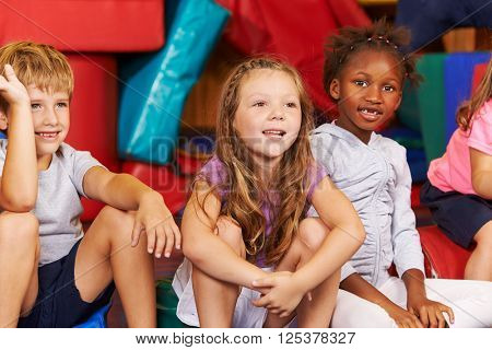 Happy group of children sitting together in a gym of an elementary school