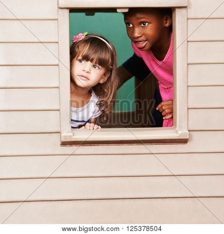 Two girls playing together in a playhouse and looking through the window