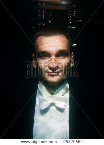 portrair of young man in bow tie and tail-coat underwater on the black background