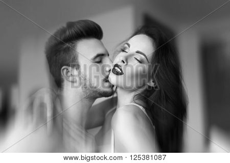Macho young man kissing sexy milf woman neck black and white