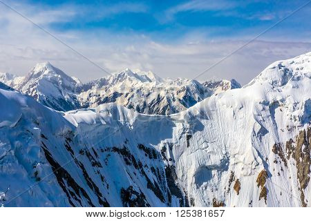 Aerial View of High Altitude Snowbound Mountains with Massive Glaciers Sharp Rock Ridges and Ice Slopes