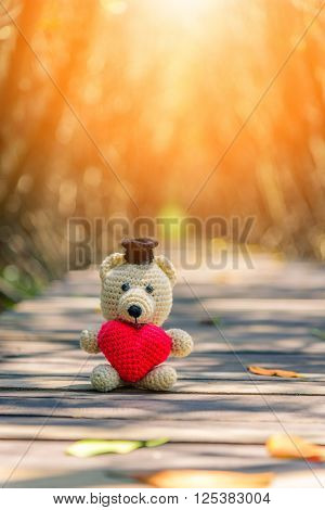 Teddy Bear with red heart sitting on wooden bridge. Vintage tone