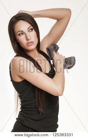 Portrait of good looking brunette woman in sports outfit. Fit woman wiping her underarm pits with towel.