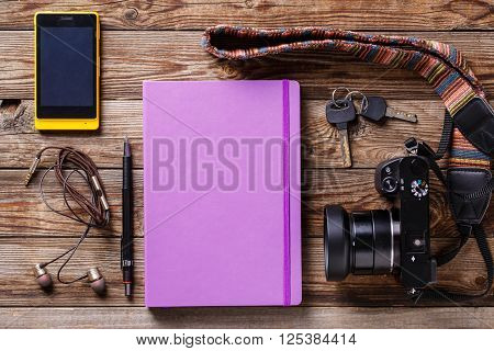 Overhead view of travel gear placed on wooden table. Mobile phone, earplugs, violet sketchbook, pencil and camera. Flat lay top view.