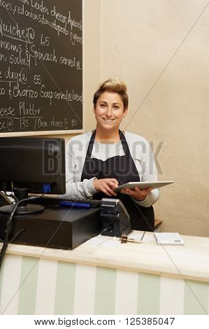 A young deli worker standing behind the counter while working on her tablet