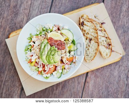 Overhead shot of a fresh salad consisting of chicken, avocado, sundried tomatoes and other tasty ingredients on a wooden table with freshly sliced bread alongside