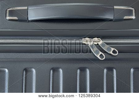 Closeup top view of silver zipper of hard shelled suitcase, new and clean luggage in black color made of Polycarbonate material