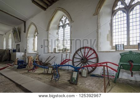 ROMNEY MARSH, KENT, UK, 25 FEBRUARY 2016 - Various antique farming equipment on display inside a church