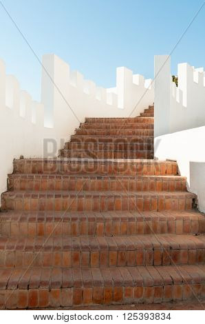 Outdoor Masonry Stairway With White Crenellated Walls At A Luxury Resort