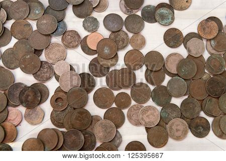 Wide assortment of old Burmese coins in various states of tarnish and corrosion scattered over a white background.