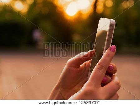 Hands of a woman using her smart phone at bright warm sunset lighting.