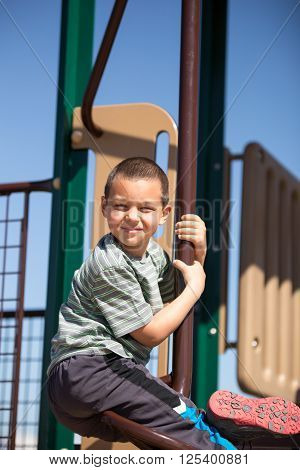 Young elementary age boy playing at the park.