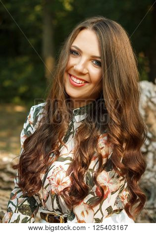 Portrait of happy brunette girl poses on nature outdoors
