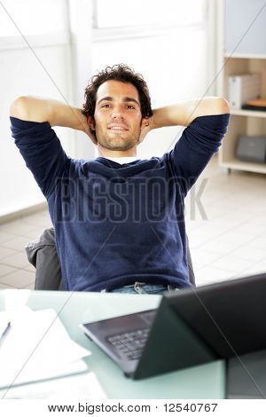 Portrait of a smiling young man relaxing in front of a laptop computer